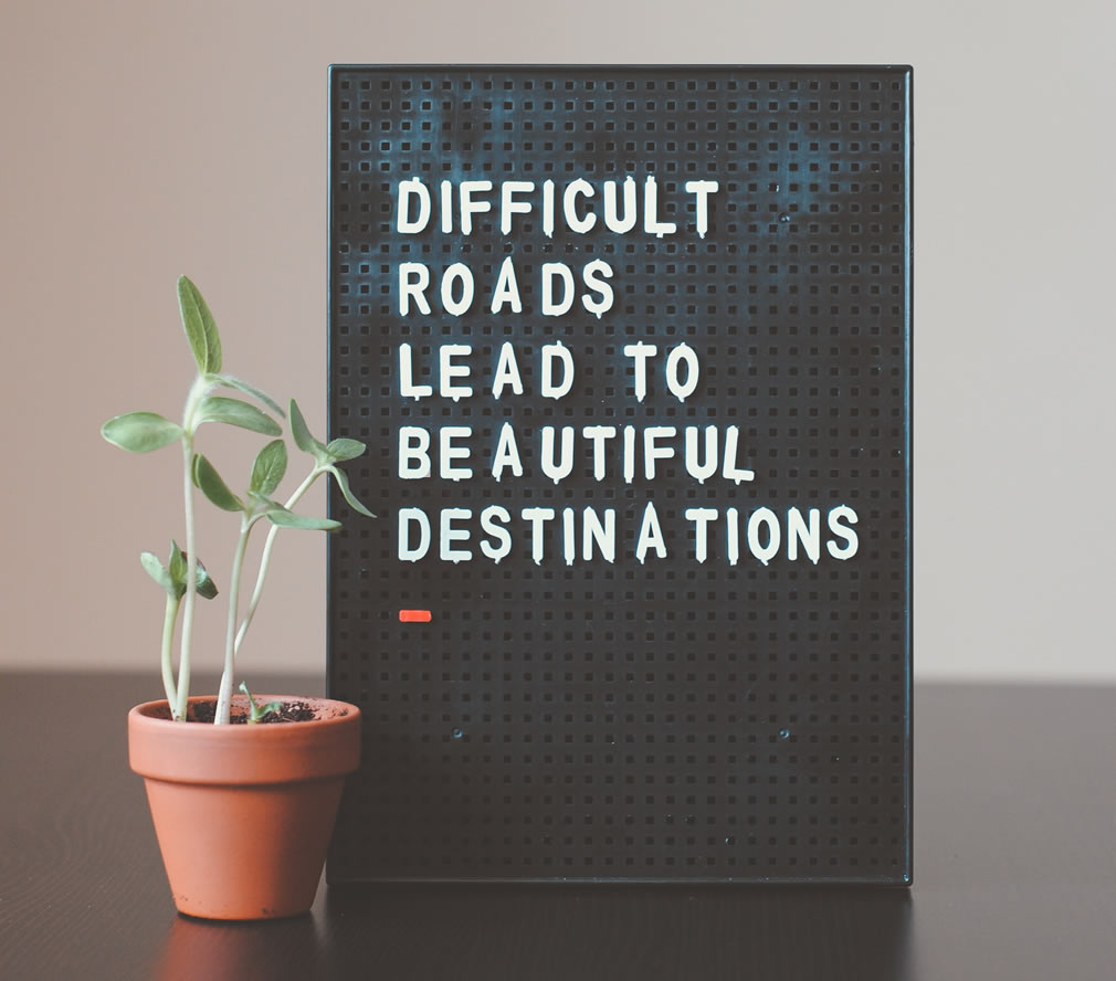 Photo of a sign that says Difficult roads lead to beautiful destinations.